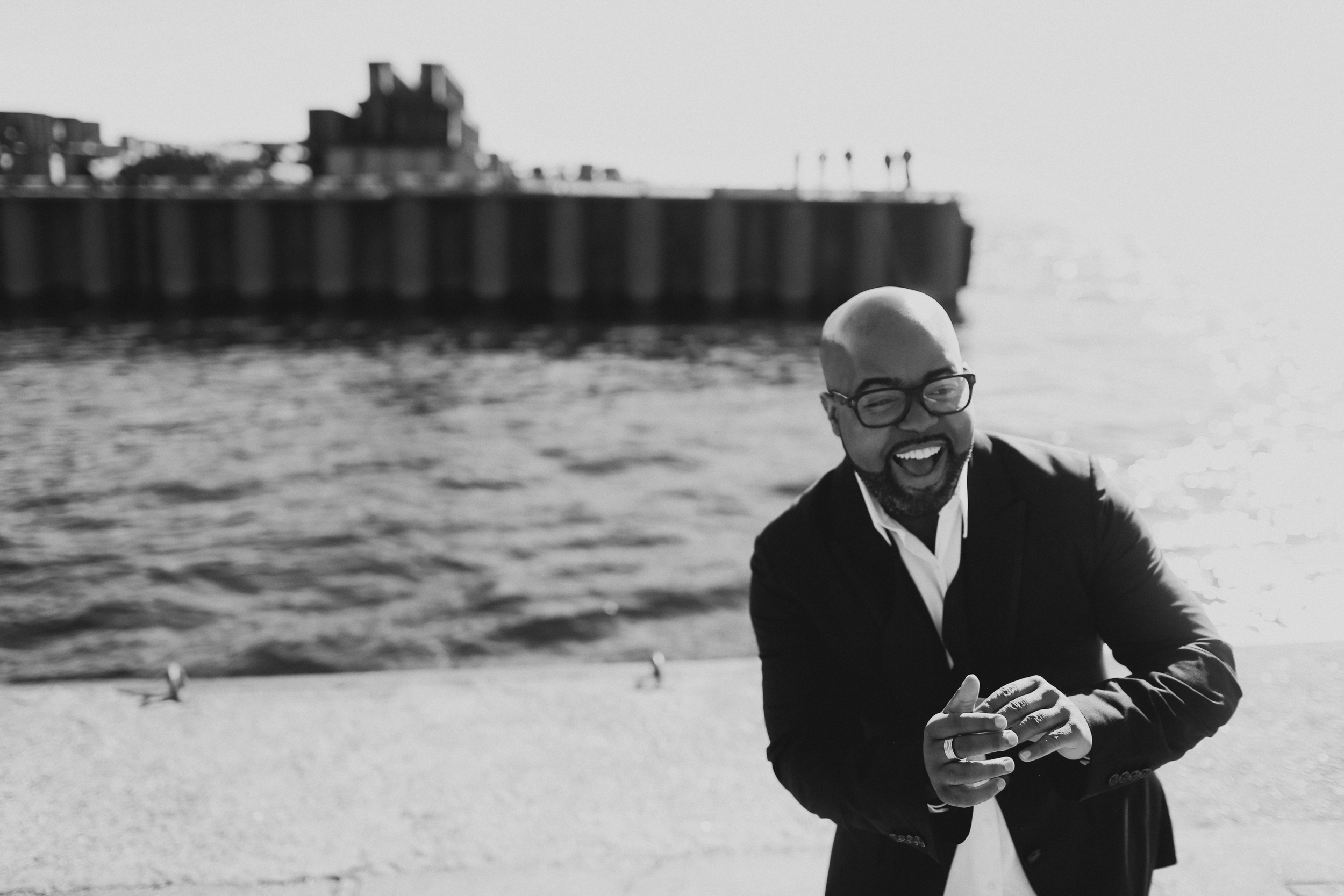 NYC vocalist C. Anthony Bryant laughing during portrait by the harbor.