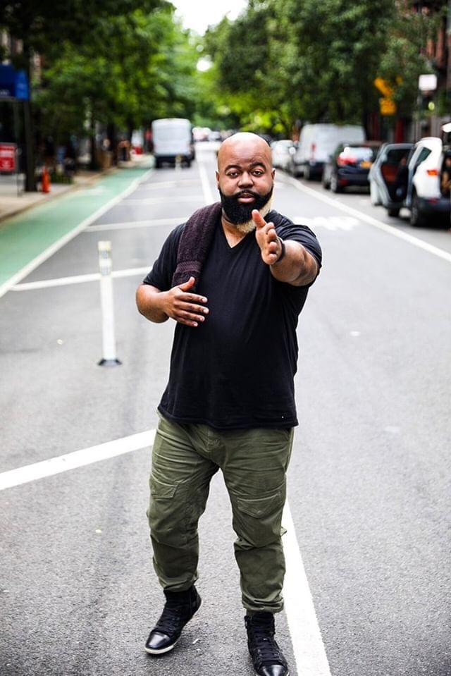 C. Anthony Bryant standing in the middle of a New York City street pointing towards the camera