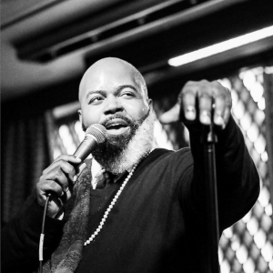 Black and white portrait of C. Anthony Bryant singing on stage with microphone at Ginny's Supper Club in Harlem NYC.